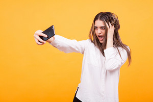 Happy young girl making a selfie over yellow background. Enjoying herself