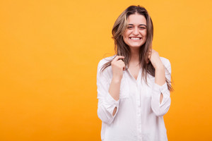 Happy young girl with big smile over yellow background. Cute girl