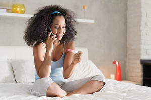 Happy young latina woman holding pregnancy test kit, sitting on bed at home. She calls her partner with mobile phone to share good news.