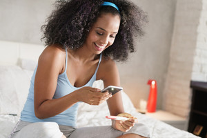 Happy young latino woman taking photo of pregnancy test kit with mobile phone and posting picture on social media. Girl sending text message with smartphone.