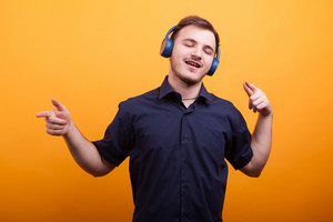 Happy young man in blue shirt listening music on headphones over yellow background. Handsome man