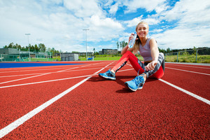 Happy Young Woman Drinking Water On Running Tracks