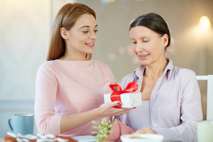 Happy young woman giving present to her aged mother