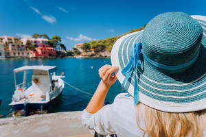Happy young woman holding straw hat enjoying vacations in Assos village in front of emerald bay of Mediterranean sea white boat and beautiful traditional houses of in Kefalonia, Greece