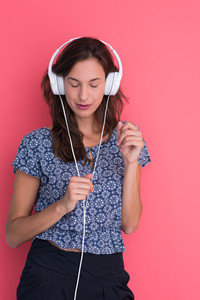 Happy young woman listening and enjoying music with headphones isolated on a red background