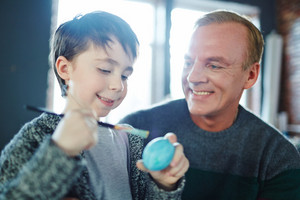 Happy youngster painting Easter egg with his father looking at him