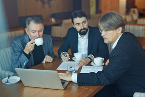 Hard-working bearded colleagues preparing business presentation on laptop while having coffee break in spacious restaurant, waist-up portrait
