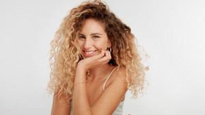 head and shoulders plan of blonde wooman with big curly hair in studio on white laughing