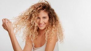 head and shoulders plan of blonde wooman with big curly hair in studio on white pull her hair aside