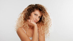 head and shoulders plan of blonde wooman with big curly hair in studio on white tilted her head and watching to the camera