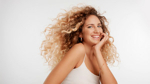 head and shoulders plan of model with big curly blonde hair in studio and blowing hair happy smiling wide