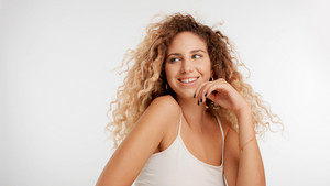 head and shoulders plan of model with big curly blonde hair in studio and blowing hair smiling wide and watching aside