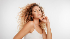 head and shoulders plan of model with big curly blonde hair in studio and blowing hair watching to the camera