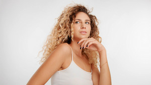 head and shoulders plan of model with big curly blonde hair in studio and watching straight