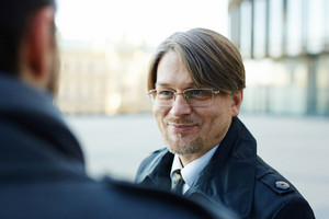Head and shoulders portrait of cheerful middle-aged businessman chatting with his colleague animatedly while standing at office building, over shoulder view