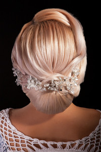 Head of woman iwith hair in weeding bun on black background. Bridal coiffure. Stylish hairstyle.