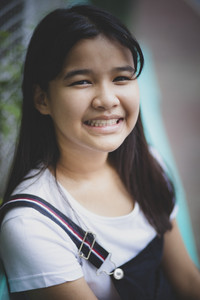 headshot of asian teenager toothy smiling with happiness emotion