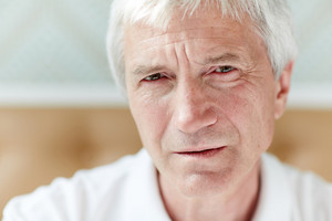 Headshot of confident senior man with frowning facial expression looking at camera, blurred background