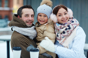 Healthy family of three in winterwear looking at camera