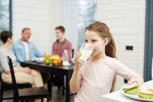 Healthy girl drinking milk from glass in the kitchen