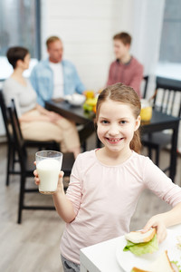 Healthy girl with glass of milk and sandwich looking at camera
