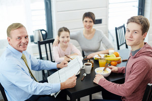 High angle view of lovely family posing for photography while eating healthy breakfast at home, waist-up portrait