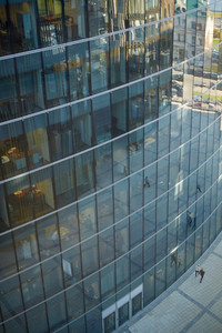 High angle view of modern glass office building, unrecognizable businesspeople passing by it