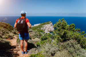 Hiking tourist man in front of beautiful seascape. Hiker trekking with backpack on rocky trail path. Healthy fitness lifestyle outdoors concept on mediterranean island