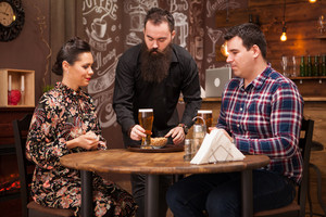 Hipster barman giving the order to beautiful young couple. Great Pub.