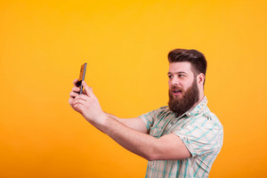 Hipster bearded man having a video call on his phone over yellow background. Expressive man.