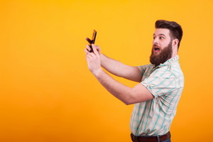 Hipster bearded man making a selfie over yellow background. Stylish beard. Cheerful young man.