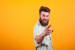 Hipster bearded man pointing with right hand at the camera over yellow background. Stylish man.