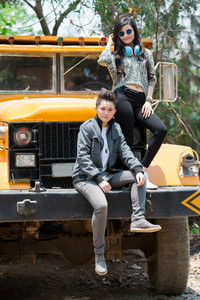 Hipster girls posing on a huge truck together outdoors