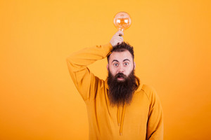 Hipster man with long beartd looking at the camera while holding a light bulb over his head. Smart solution. Handsome man.
