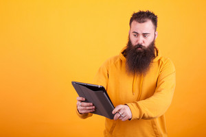 Hipster with long beard looking at tablet over yellow background. Looking confused