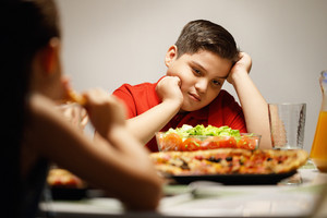 Hispanic family with mom, fat son and daughter having dinner at home, eating salad and pizza. Latino people with mother, overweight boy and girl during meal