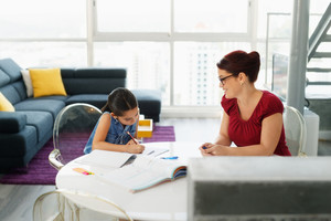 Hispanic mother and female child, with mom helping daughter with school homework