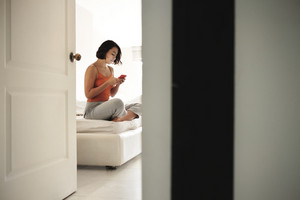 Hispanic woman sitting in bed at home with smart phone. Girl addicted to social media, checking her account on mobile phone in bedroom at morning.