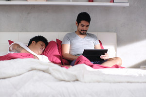 Homosexual couple, gay people. Man playing video game with computer in bed and partner sleeping
