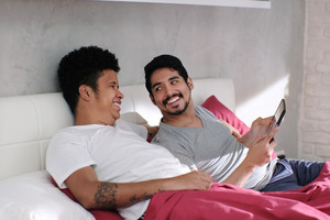 Homosexual couple, gay people. Man streaming movie on laptop computer in bed, watching show with his partner