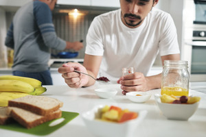 Homosexual couple, gay people, same sex marriage between hispanic men. Male partners having breakfast and cooking in kitchen at home