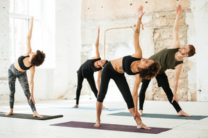 Horizontal image of young people doing yoga exercose in light gym