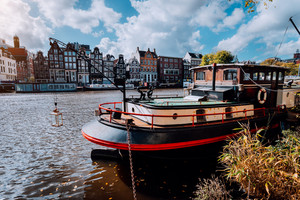 Houseboat and traditional leaning buildings along the canal in Amsterdam
