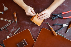 Human hands using handtool while producing leather item