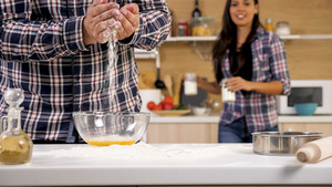 HUsband having fun with flour while his wife looks away. Happy couple