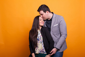 Husband kissing his wife forehead over yellow background. Happy couple. Showing affection.