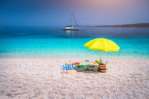 Idyllic white beach with green yellow umbrella on lazy summer day. Sailing boat at anchor in calm crystal clear blue sea water