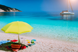 Idyllic white beach with umbrella on lazy summer day. Sailing boat at anchor in calm crystal clear blue sea water
