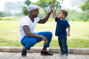 Image of a modern father giving a hi-five his little son in the park