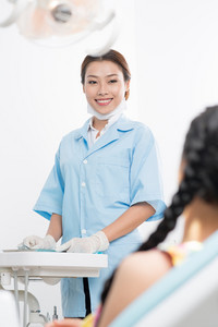 Image of a smiling dental assistant and back view of her patient sitting in the dental chair